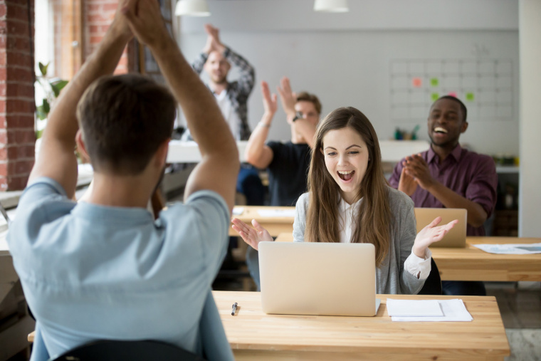 girl being applauded for succeding at work - how to retain workers - open office with young people - frezza magazine